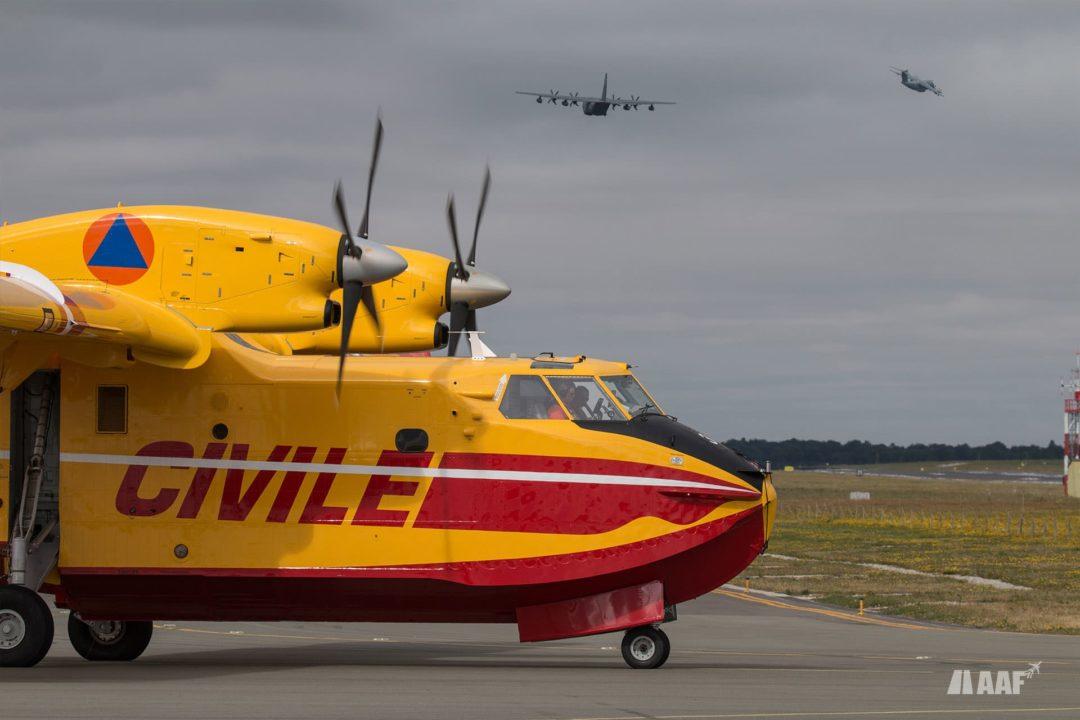 Avion bombardier d'eau Bombardier CL415 Canadair au roulage alors qu'un KC130J et un A400M décollent pour rejoindre le circuit d'attente